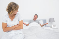 Angry woman looking at husband gesturing during a fight Stock Photo