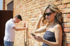 Angry woman looking phone and man posing on wall stock photo