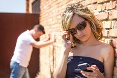 Angry woman looking phone and man posing on wall Royalty Free Stock Photos