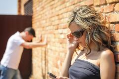 Angry woman looking phone and man posing on wall Stock Image