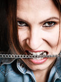 Angry woman mad girl biting metal chain. Negative emotions. Face of emotional angry woman. Portrait of mad girl biting metal chain royalty free stock photo