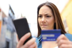 Angry woman paying with credit card and phone outside stock photos