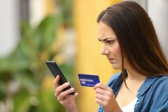 Angry woman paying with credit card and smart phone outdoors. In a colorful street royalty free stock photo