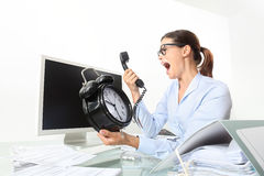 Angry woman at phone in office desk with clock, computer Stock Image