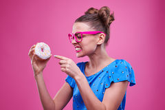 Angry woman pointing at the doughnut over pink background Royalty Free Stock Photography