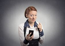 Angry woman pointing with finger at smart phone. Closeup portrait angry young business woman annoyed worker pissed off employee while on mobile pointing with Royalty Free Stock Photo
