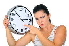 Angry Woman Pointing To Clock. Angry woman or mom pointing at clock showing 3 o'clock stock photo