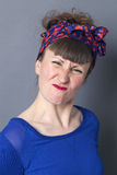 Angry woman pouting and frowning, being frustrated and exasperated. Portrait of an angry brunette woman with bangs and a fifties scarf as retro hairstyle pouting stock image