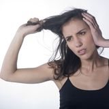 Angry woman pulling her hair. Studio portrait of a pretty woman pulling her hairs with a frustrated expression on face Royalty Free Stock Photography