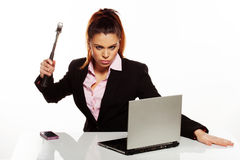 Angry woman raising a hammer to her laptop Royalty Free Stock Photo