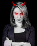 Angry woman with red eyes and devil horns. Crazy, angry  woman with red eyes and devil horns over black background Stock Image