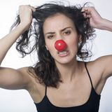 Angry woman with red nose. Portrait of a very furious woman wearing red nose Stock Image