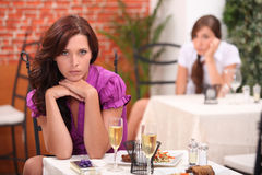 Angry woman at the restaurant. Angry women at the restaurant, on the table,  an unopened gift and flutes of sparkling wine Stock Photos