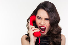 Angry woman in retro style screaming and talking on telephone. Close up of angry mad curly young woman in retro style screaming and talking on telephone over Stock Images