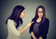 Angry woman scolding her scared shy sister or friend. Angry women scolding her scared shy young sister or friend isolated on gray wall background Stock Photography