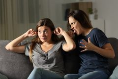 Angry woman scolding to another ignoring her. Angry women scolding to another ignoring her sitting on a couch in the living room at home Royalty Free Stock Photography