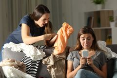 Angry woman scolding to her messy roommate. Angry women scolding to her messy roommate sitting on a couch in the living room at home royalty free stock photos