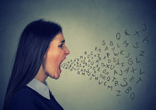 Angry woman screaming alphabet letters flying out of open mouth. Side profile portrait of young angry woman screaming with alphabet letters flying out of wide stock images
