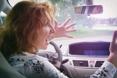 Angry woman screaming while driving a car. Angry woman screaming and gesturing while driving a car. Negative human emotions concept Royalty Free Stock Images