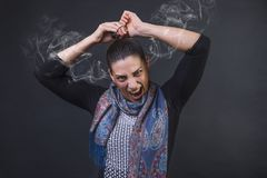 Angry woman screaming in frustration, furious unable to tie her pony tail and steaming out of her ears. Angry woman screaming in frustration furious unable to Royalty Free Stock Photo