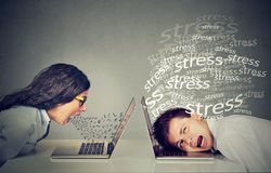 Angry woman screaming at laptop sitting next to a stressed man. Side profile angry women screaming at laptop sitting next to a stressed man. Negative emotion Royalty Free Stock Photography