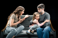 Angry woman screaming at little daughter hugging with father. Angry women screaming at little daughter hugging with father, family problems concept Royalty Free Stock Photography