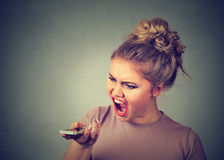 Angry woman screaming on mobile phone. Stock Photos