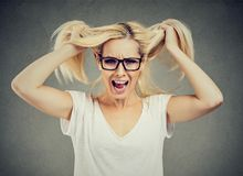 Angry woman screaming out loud and pulling her hair out Stock Photography