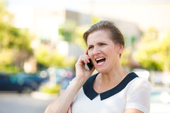 Angry Woman Screaming on a Phone Royalty Free Stock Photography