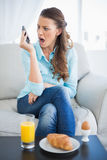 Angry woman screaming on the phone sitting on sofa. In bright living room Stock Photos