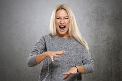 Angry woman screaming with rage. On a concrete gray background Stock Photo