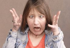 Frustrated woman lets out her pent up anger. Angry woman screaming with rage, furious and dangerous Stock Photos