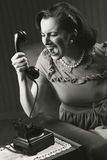 Angry woman screaming at retro phone Stock Images