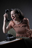 Angry woman. Screaming at retro phone, 1950 style stock image