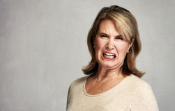 Angry woman. Angry screaming senior woman over gray wall background Stock Photo
