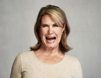 Angry woman. Angry screaming senior woman over gray wall background stock image