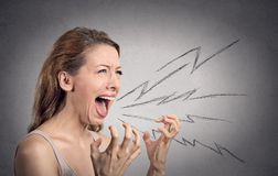 Angry woman screaming. Side view portrait angry woman screaming, wide open mouth, hysterical  grey wall background. Negative human face expressions, emotion, bad Royalty Free Stock Photography