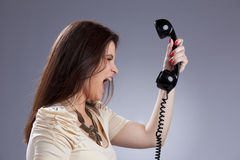 Angry woman screaming to the telephone. Furious young woman shouting to the telephone handset Royalty Free Stock Image