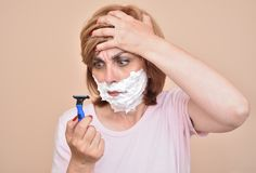 Angry woman with shaving foam on her face holding and looking at a razor stock images