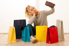 Angry woman with shopping bags after shopping as she spent all t. He money Royalty Free Stock Photography