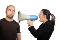 Angry woman shouting. Portrait of angry woman shouting at his boyfriend through megaphone who is indifferent to it Stock Images