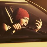 Angry woman shouting on cell phone driving a car. Angry woman in red beanie shouting on cell phone driving a car royalty free stock photo