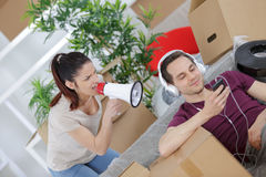 Angry woman shouting at husband with megaphone Royalty Free Stock Photo