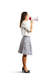 Angry woman shouting at megaphone. Isolated on white background Stock Images