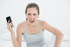 Angry woman shouting with mobile phone in hand on bed Stock Image