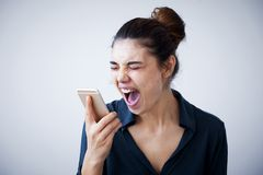 Angry woman shouting on phone on gray background. Angry woman shouting  on phone on gray background Royalty Free Stock Photography