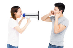 Angry woman shouting at young man on horn loudspeaker. Angry women shouting at young men on horn loudspeaker on white background Stock Images