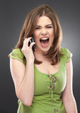 Angry woman shouts in phone  on gray Stock Photos