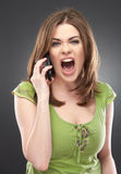 Angry woman shouts in phone isolated on gray Royalty Free Stock Photos