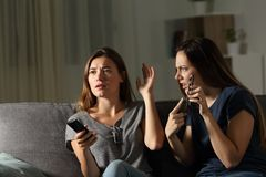 Angry woman showing phone and friend ignoring her. Angry women showing phone and friend ignoring her sitting on a couch in the living room at home Stock Image